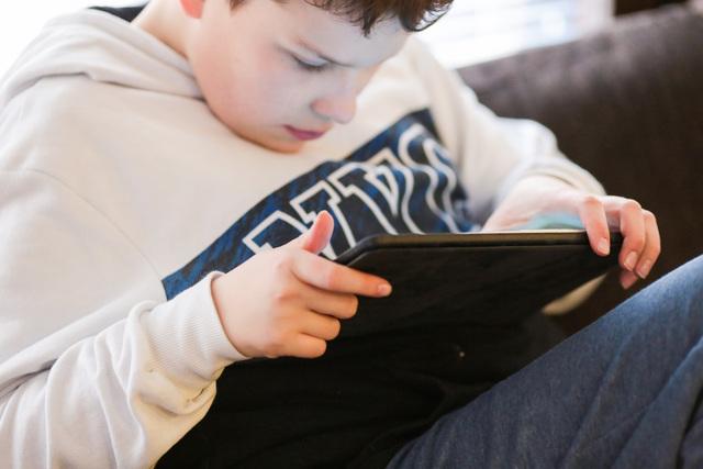 Poika istuu sohvalla ja selaa tablettia. Lyhytaikaishoito Haminan Ravimäessä mahdollistaa mukavan paikan omaishoidettavalle omaishoitajan vapaan ajaksi.