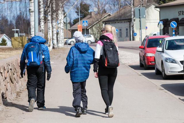 Kaksi lasta kävelee ohjaajan saattamana kevätvaatteissa iltapäivähoitoon Ravimäkeen. Iltapäiväkerho Haminan Ravimäessä toimii kouluvuoden aikana maanantaista perjantaihin.
