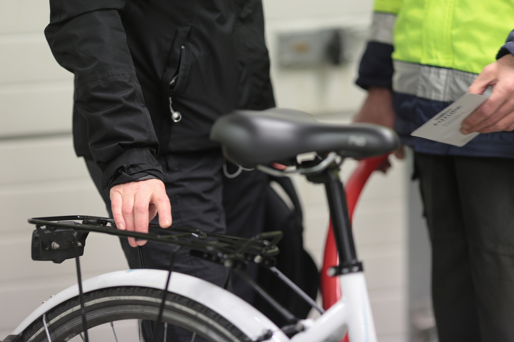 Kaksi ihmistä juttelee, toinen pitää kättään valkoisen polkupyörän tarakalla. Polkupyörähuolto Haminassa hoituu myös Ravimäen Työpalvelussa.