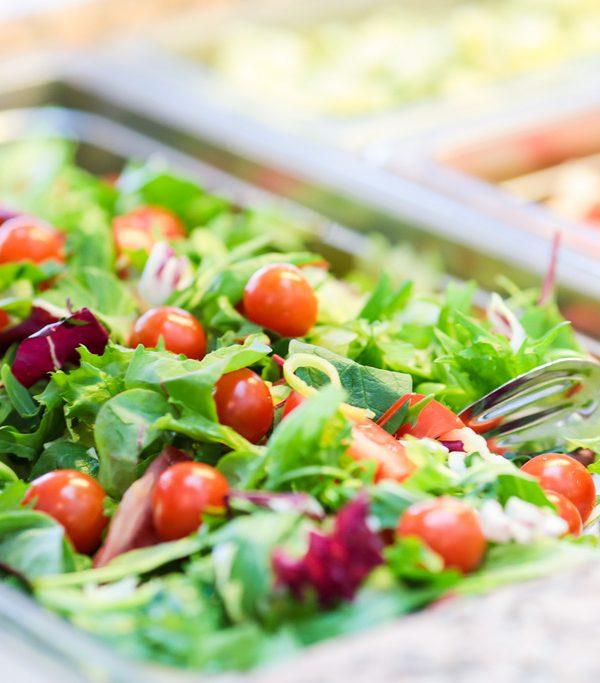 Suuri, vihreä salaatti, jossa on punaisia kirsikkatomaatteja. Ravimäen ravintolapalvelut järjestävät vaikka häät tai ristiäiset ravintoloissaan Haminassa.